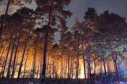 Zásah hasičov pri lesnom požiare komplikujú zvyšky nevybuchnutej munície v lese.