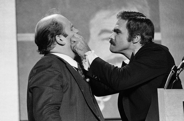 Na archívnej snímke z 2. decembra 1977 americký herec Burt Reynolds štípe na líce komika Doma Deluiseho v Atlante.