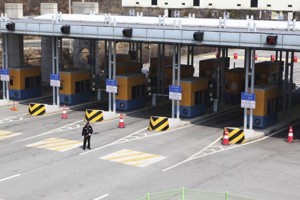 Juhokórejský strážnik stojí pred zavretými vstupnými bránami do severokórejského mesta  Käsong.