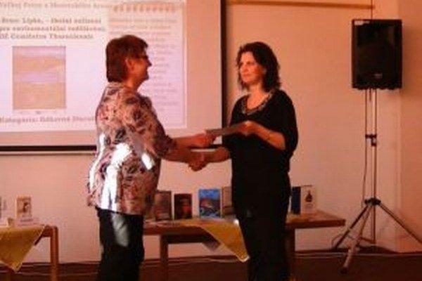Lucia Jesenská zo Štúdia LJ (vpravo) preberá ocenenie v súťaži Kniha Turca 2014 od riaditeľky Turčianskej knižnice K. Vandlíkovej.