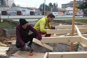 Študenti Lívia a Tomáš z SPU pri úprave okolia fontány pred súdom.