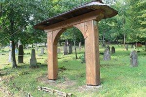 Cintorín v Hornom Tisovníku s replikou vstupnej brány. Originál pôvodne stál na cintoríne vo Veľkom Lome.
