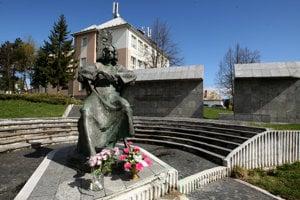 Socha Mateja Bela, v pozadí budova školy v Očovej.