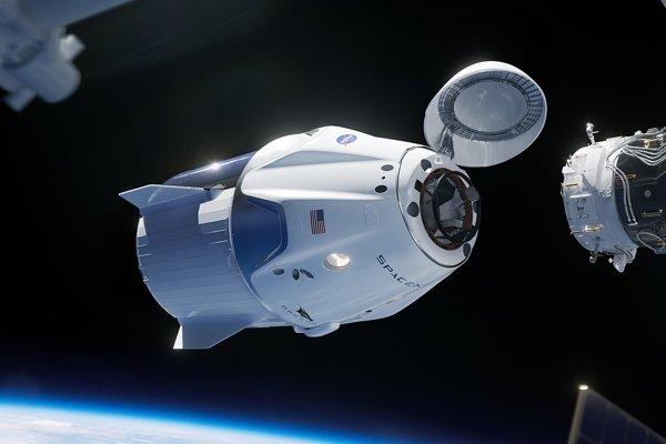 Ilustrácia kapsule Crew Dragon pri dokovaní k Medzinárodnej vesmírnej stanici.