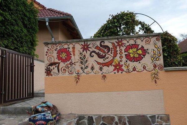 Časť maľovaného plota pred domom.
