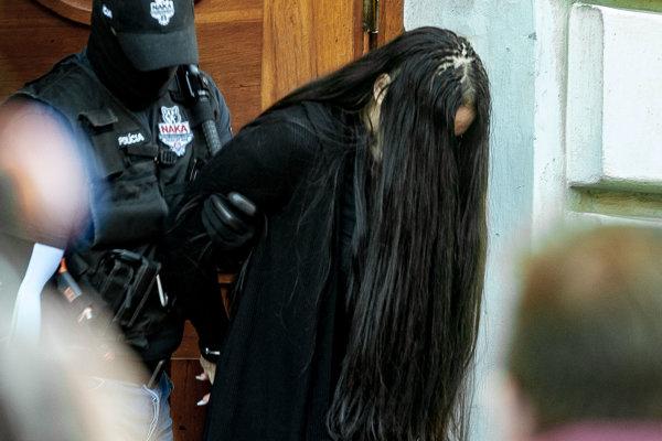 Polícia odvádza Alenu Zsuzsovú - jednu z obvinených z budovy Špecializovaného trestného súdu v Banskej Bystrici.