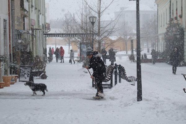 Pani Mária odpratáva sneh pre domom na Kupeckej ulici.