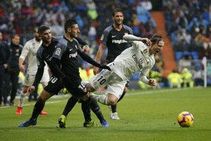 Luka Modrič je faulovaný hráčmi FC Sevilla.