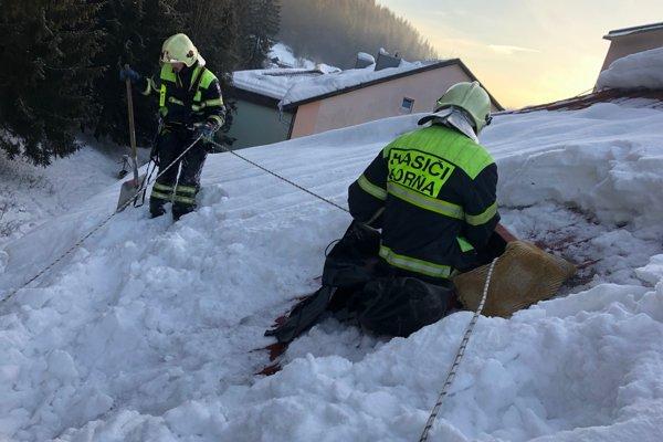 Hasiči sa snažia odbremeniť strechy od snehu.