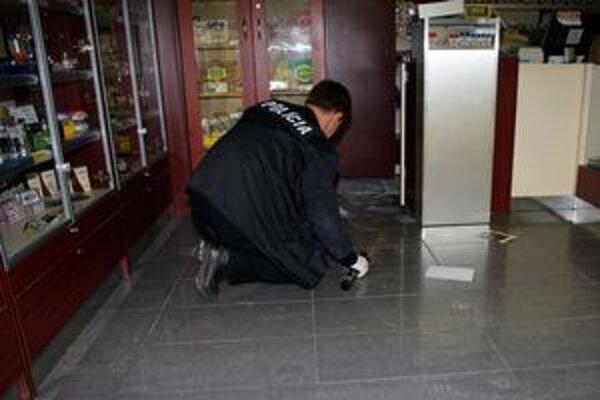 Kriminalista skúma stopy vo vykradnutej prevádzke v obchodnej zóne hypermarketu Tesco v Púchove.