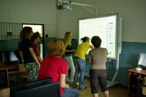 Bývalí deviataci pri interaktívnej tabuli.