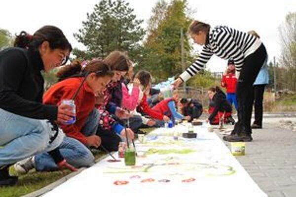 Deti s umelcami maľovali niekoľkometrový obraz na zemi.