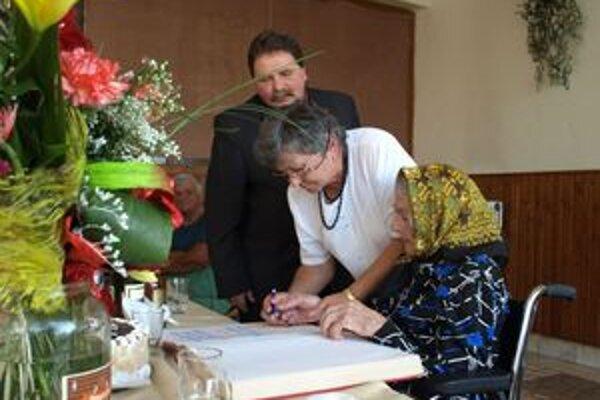 Pri podpisovaní do Pamätnej knihy obce mamke Márii Orčíkovej pomáhala jej dcéra Zlatka Verbová.