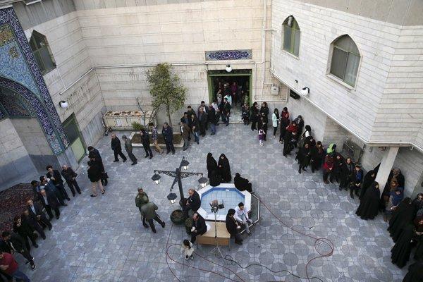Muži a ženy čakajú v radoch pred volebnou miestnosťou.
