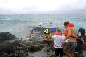 Ľudia schádzajú zo skalného brala počas pokusu o záchranu azylantov z potopenej lode v rozbúrenom mori pri austrálskom pobreží Vianočného ostrova.