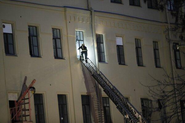 Hasič zasahuje na mieste zrútenia časti budovy univerzity v Petrohrade.
