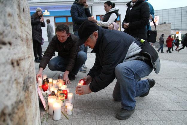 Ľudia zapaľovali sviečky.