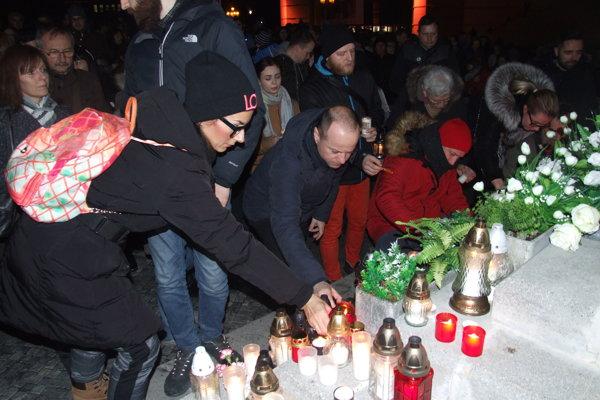 Ľudia zapaľovali sviečky a kahančeky pri Mariánskom stĺpe na námestí.