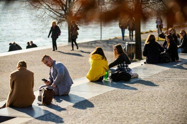 Ľudia odpočívajú na brehu Dunaja pri obchodnom centre počas slnečného dňa 28. februára 2019.
