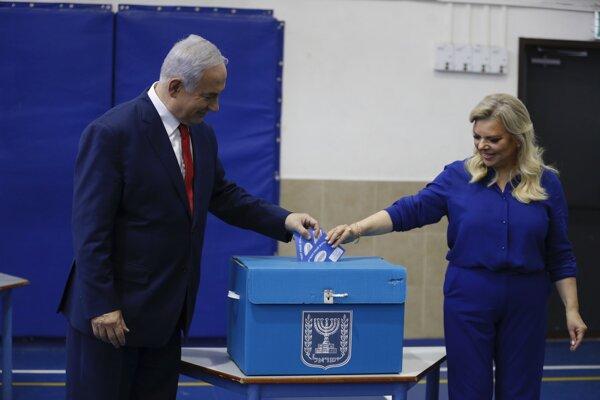Izraelský premiér Benjamin Netanjahu (vľavo) spolu so svojou manželkou Sarou hádže do volebnej schránky svoj hlas počas hlasovania v predčasných parlamentných voľbách vo volebnej miestnosti v Jeruzaleme.