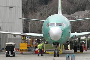 Pracovník stojí pri stroji  Boeing 737 MAX 8 zaparkovanom v montážnom závode v americkom meste Renton. (11. marec 2019)