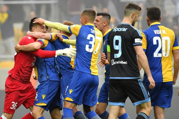 Momentka zo zápasu Dunajská Streda - Slovan Bratislava. Brankár Martin Jedlička dostáva pochvalu od spoluhráčov po chytenej penalte, pred nimi Andraž Šporar.