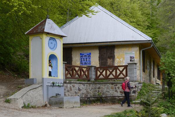 V popredí prameň sv. Jána Nepomuckého, v pozadí stará kamenná hospodárska budova.
