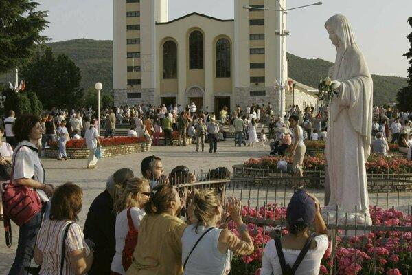 Veriaci sa modlia pri soche Panny Márie pred kostolom sv. Jakuba v bosnianskom pútnickom meste Medžugorie.