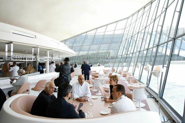 Ľudia sedia v Paris Cafe počas otvorenia hotela.