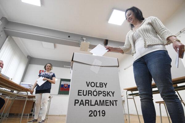 Jedna z voličiek hádže hlasovací lístok do volebnej urny.