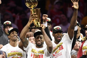 Kawhi Leonard (v popredí) zdvíha nad hlavu trofej Larryho O'Briena pre víťaza NBA 2018/2019.