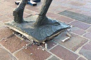 Bronzová socha má zlomenú pravú nohu a posunutý podstavec.