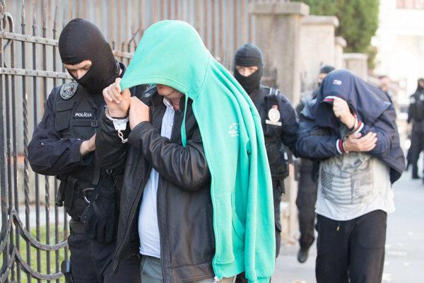 Policajti privádzajú na súd mužov, zadržaných v rámci akcie Shark