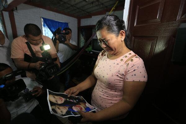 Žena ukazuje fotografiu jej nevesty, syna a vnučky, ktorých našli utopených.