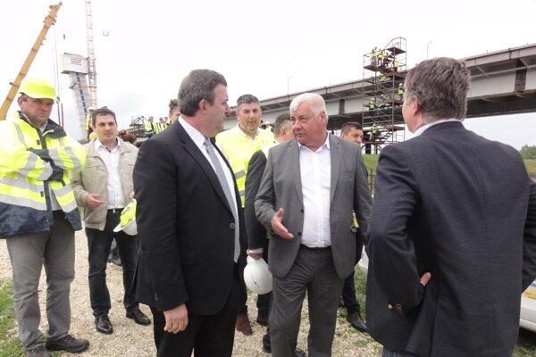 Slovenský minister dopravy Arpád Érsek (šedý oblek) a maďarský minister inovácií a technológií László Palkovics (čierny oblek) na kontroel stavby mosta.