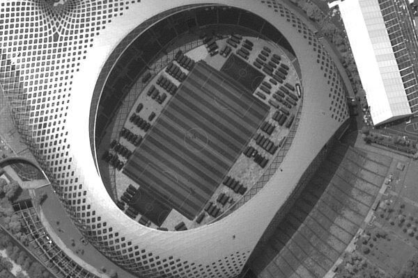 Obrovský športový štadión v meste Šen-žen je zaplnený vojenskými vozidlami.