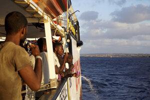 Zachránení africkí migranti stoja na palube španielskej humanitárnej lode Open Arms, ktorá sa plaví neďaleko talianskeho ostrova Lampedusa.