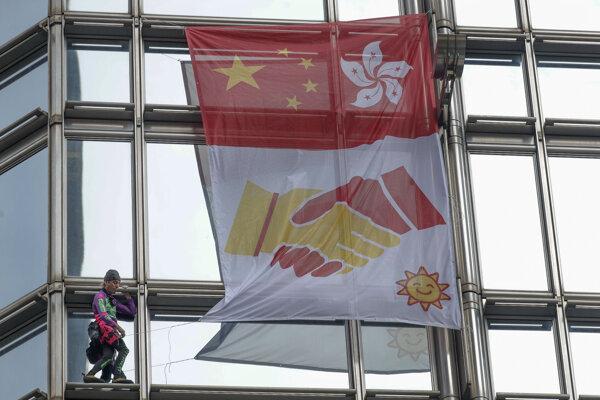 Alain Robert zavesil na mrakodrape zástavu volajúcu po mieri.
