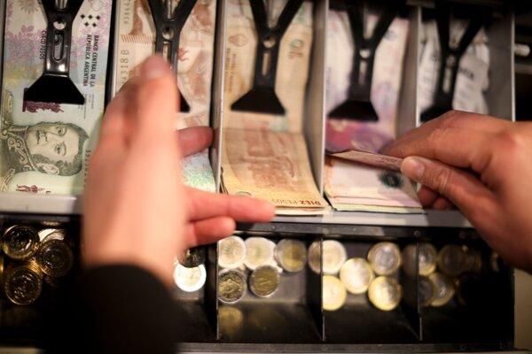 Muž ráta bankovky v hodnote 100 pesos v pokladni reštaurácie v Buenos Aires.  Peso sa do konca obchodného týždňa v piatok 16. augusta prepadlo o 21 %.