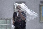 Muž v japonskom meste Iwaki bojuje s dáždnikom v silnom vetre, ktorý tajfún spôsobil.