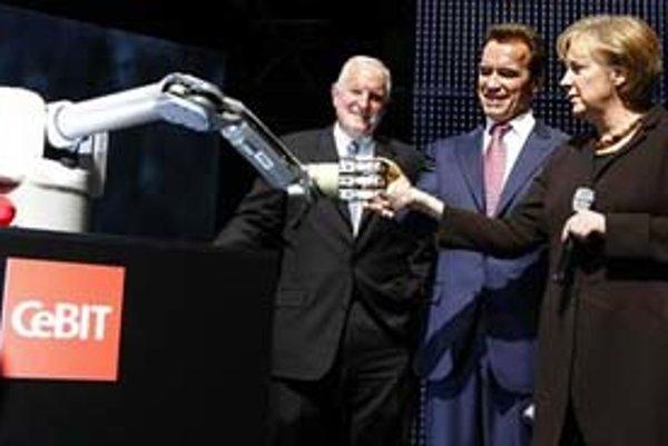 Guvernér Kalifornie Arnold Schwarzenegger a nemecká kancelárka Angela Merkelová si podávajú ruku s robotickým ramenom Marvinom na veľtrhu Cebit v Hanoveri. Po ich boku stojí predseda predstavenstva spoločnosti Intel Craig R. Barrett.