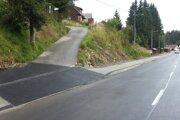 Výjazd z hlavnej cesty na vedľajšiu so žľabom na zachytávanie dažďovej vody.