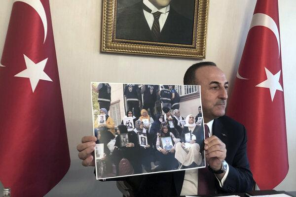 Turecký minister zahraničných vecí Mevlüt Čavušoglu ukazuje fotografiu žien, ktorých deti údajne uniesli Kurdi.