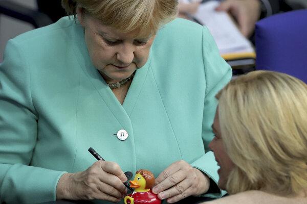 Nemecká kancelárka Merkelová sa podpisuje na kačičku, ktorá imituje jej známe gesto a šatník.