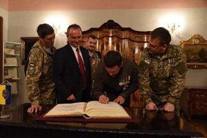 Dmitro Fesenko pri podpise do pamätnej kroniky významných hostí Košíc. Vedľa neho ambasádor MMM pre Ukrajinu Eduard Buraš.