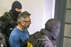 Policajti eskortujú obvineného Ľubomíra Kudličku zo skupiny tzv. takáčovcov do pojednávacej miestnostni Špecializovaného trestného súdu v Banskej Bystrici.