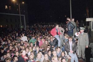 Na snímke z 10.novembra 1989 obyvatelia Východného a Západného Berlína stoja pri hraničnom plote na hraničnom priechode vo Východnom Berlíne.