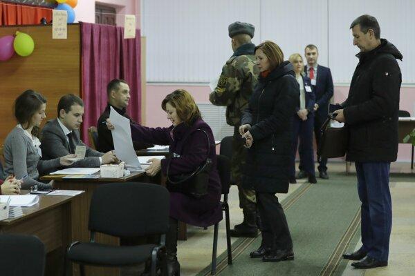 Bieloruskí voliči dostávajú hlasovacie lístky počas hlasovania v parlamentných voľbách vo volebnej miestnosti v Minsku 17. novembra 2019.