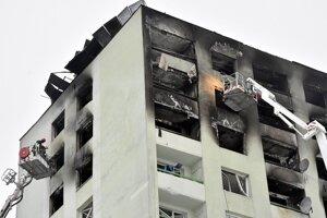 Hasiči pomocou vysokozdvižnej plošiny prehľadávajú byty a hľadajú v troskách panelového domu pozostatky obetí ničivého výbuch plynu.