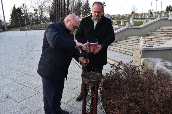 Prvý tajomník Veľvyslanectva Ruskej federácie v Slovenskej republike Anatolij A. Tomnikov (vľavo) vzal hrsť zeme s vojnového cintorína v Humennom.